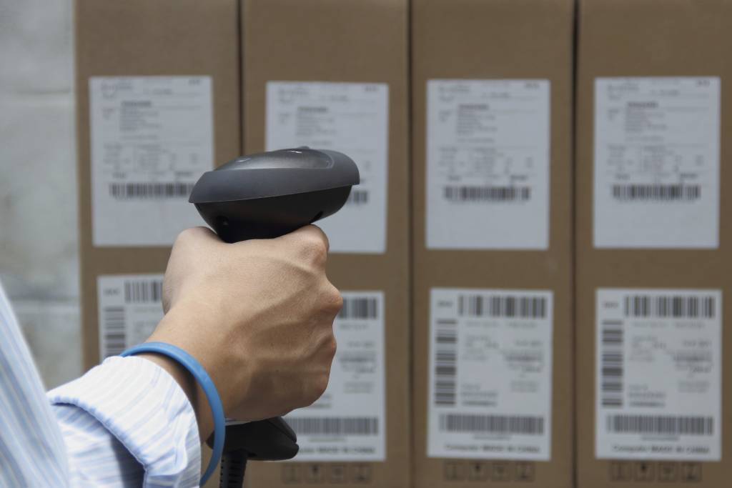 Holding barcode scanner with a label on the boxes- category expertise of brand and retail shares
