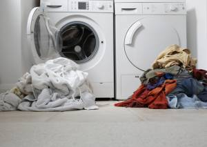 Washer and Dryer with piles of white and colored laundry